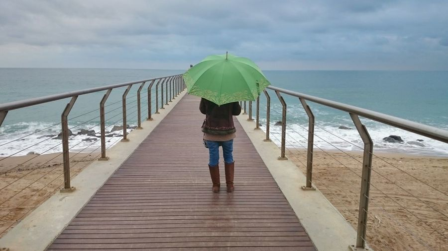 Rear View Of Woman Holding Umbrella While Standing On Pier At Beach