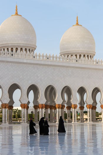 Abu Dhabi, United Arab Emirates - October 10,2014: Women walking on the Sheikh Zayed Grand Mosque Abu Dhabi Arabic Arch Architecture Building Exterior Built Structure Dome Faith Famous Place Grand Mosque Islam Memories Men Mosque People Person Place Of Worship Religion Sheik Zayed Mosque Spirituality Tourism Travel Destinations United Arab Emirates Water White Mosque