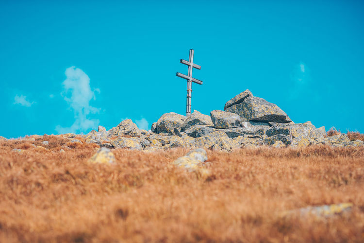 Dumbier peak. Double cross on a highest point of Low Tatras Cross Double Cross Dumbier Beauty In Nature Blue Cloud - Sky Communication Day Grass Land Low Angle View Nature No People Non-urban Scene Outdoors Peak Rock Rock - Object Scenics - Nature Sign Sky Solid Tranquil Scene Tranquility Turquoise Colored