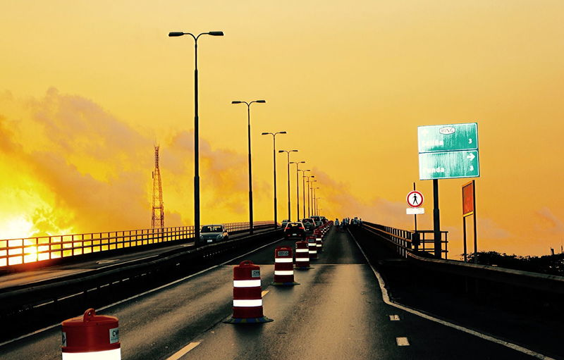 Juliana Bridge in Willemstadt, Curacao before sunrise Bridge - Man Made Structure Car City Connection Contre-jour Day Highway Horizon Juliana Bridge Lighting Equipment Mode Of Transport No People Outdoors Road Road Sign Sky Street Light Sunset Surreal Atmosphere Transportation Travel Twilight Yellow Dawn