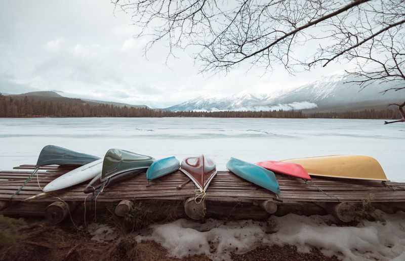 Boats Moored By Frozen Lake Against Cloudy Sky During Winter