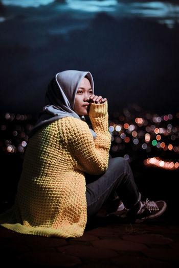 Thoughtful woman wearing hijab sitting outdoors