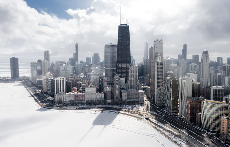 Aerial view of buildings in city against sky during winter