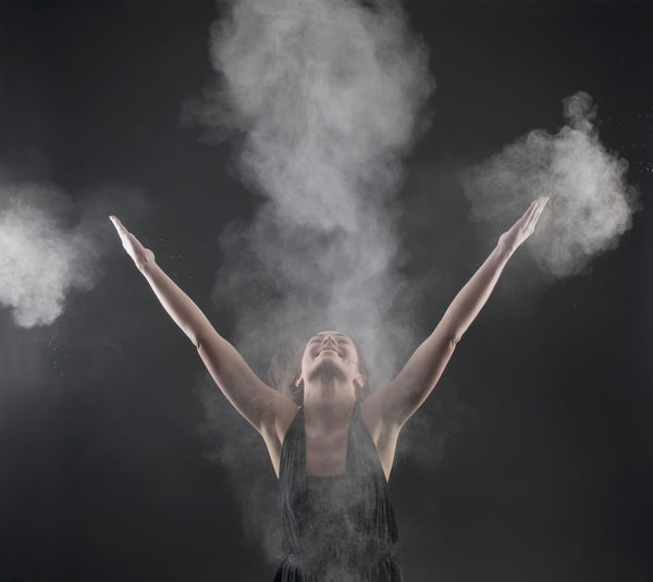 Close-up of woman with arms raised standing amidst talcum powder against black background
