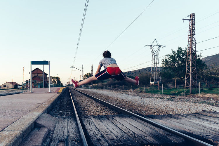Rear View Of Woman Jumping Over Railroad Tracks Against Clear Sky