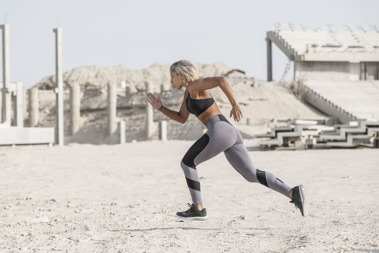 Middle Eastern Girl with short braided hair sprinting in a construction site wearing gray and black fitness outfit on a hot bright sunny day. Exercising Jumping Off Rocks Sitting Adult Architecture Beautiful Woman Bright Day Built Structure Day Dusty Effort Exercising Fitness Model Focus On Foreground Full Length Healthy Lifestyle Hot Day ☀ Land Leisure Activity Lifestyles Middle Eastern Woman Nature One Person Outdoors Real People Side View Sport Sports Clothing Stretching Young Adult Young Women