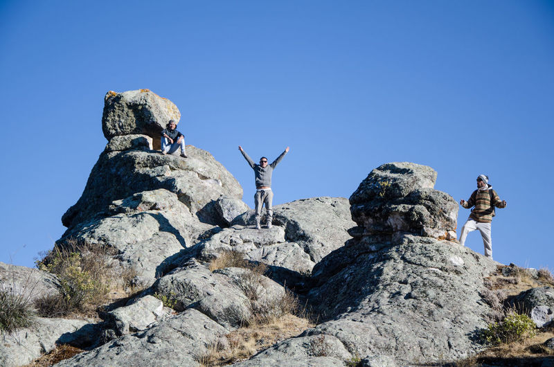 Low angle view of people on rock against clear sky