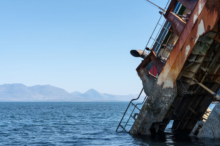 Scotland Wreck Architecture Blue Boat Built Structure Clear Sky Copy Space Day Island Isle Of Skye Men Mode Of Transportation Mountain Nature Nautical Vessel Occupation Outdoors Real People Sea Ship Sky Transportation Water Waterfront The Great Outdoors - 2018 EyeEm Awards The Photojournalist - 2018 EyeEm Awards The Traveler - 2018 EyeEm Awards