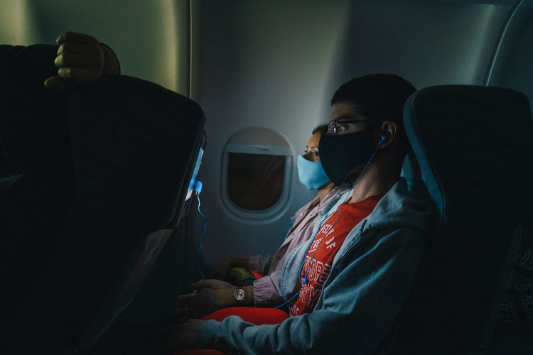 People wearing mask sitting in airplane