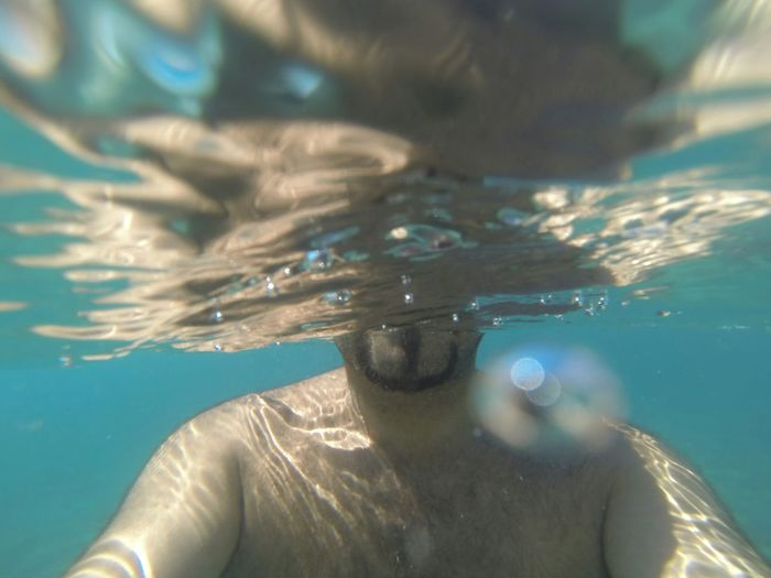 Midsection of man swimming in sea