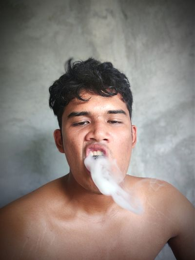 Portrait of shirtless young man smoking against wall