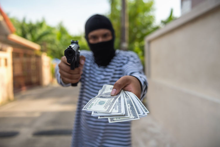 Thief Holding Paper Currency And Handgun