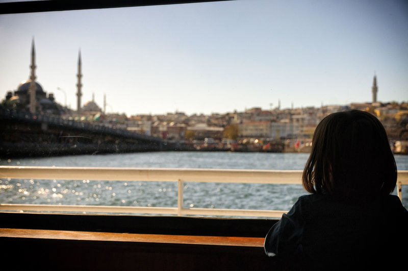 Rear View Of Girl In Ship Looking At Cityscape