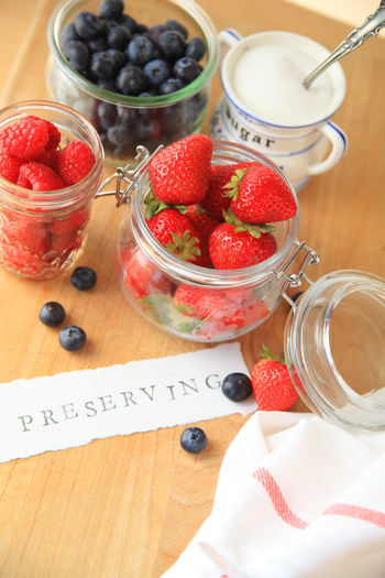 Preserving word with colorful summer berries Blueberries Bowl Close-up Colorful Cooking Dish Towel Fabric Fresh Fruit Freshness Glass Jars Indoors  Natural Light No People Overhead Paper Preserving Red Still Life Strawberries Sugar Sweet Food Table Wood - Material Word