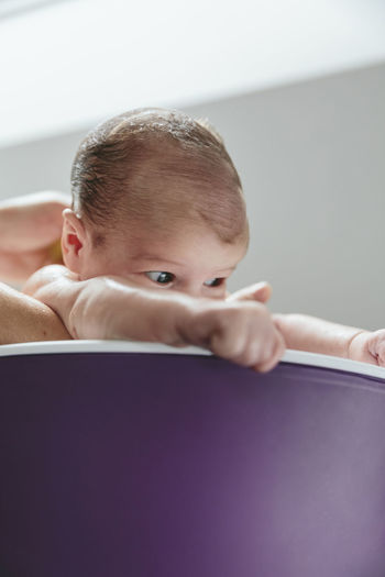 Newborn girl in the bathtub held by her mother upside down Beautiful Baby Newborn Portrait Waist Up Relaxed Child Cute Innocence Girl Care Little Mom Family One Person Real People Caucasian Water Bathtub Bathing Bath Belly Button Umbilicus Hygiene Vertical