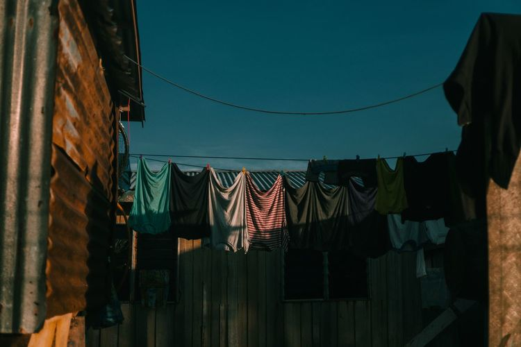 Low angle view of clothes hanging on rope against sky