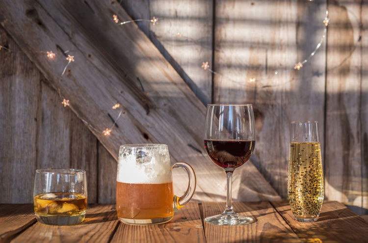 variety of alcoholic beverages sitting on rustic barn wood background Barn Beer Champagne Drinks Entertaining Event Invite Lights Reception Rustic Wedding Whisky Alcohol Bar Bourbon Choices Invitation Open Bar Party Room For Text Scotch Selection Whiskey Wine Wood - Material