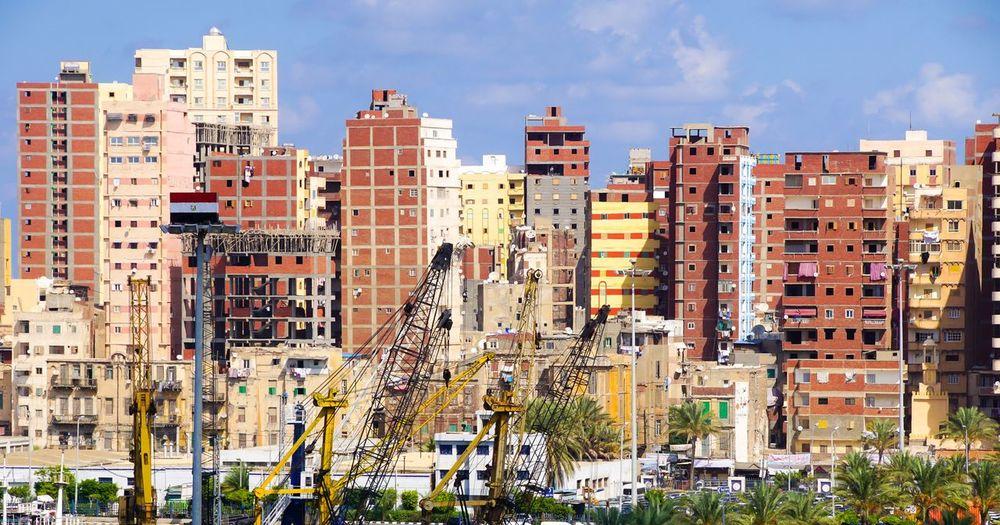 Cranes Against Buildings In City