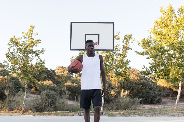 Young African man holding basketball and looking away on background of sports ground. African Athlete Athletic Basketball Confidence  Determination Ethnicity Man Recreation  Sportsman Ball Black Concentrated Confident  Healthy Holding Player Posing Posture Professional Serious Sport Sportive Sportsground Streetball