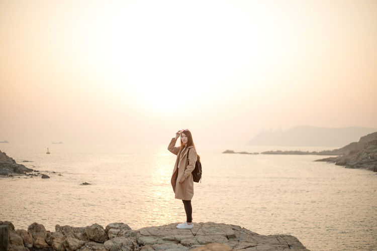 Hairstyle Outdoors Beach Dress Fashion Land Young Adult Leisure Activity Beauty In Nature Women Nature Adult Solid Sea Rock Rock - Object Sky Standing Water One Person Full Length Scenics - Nature Lifestyles Real People