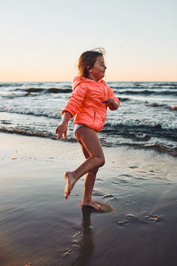 Playful little girl enjoying a free time over sea on a sand beach at sunset during summer vacation