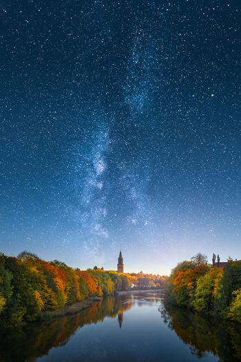Scenic view of river amidst trees against star field in sky during autumn