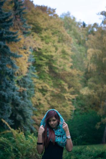 Woman wearing headscarf standing on field against trees