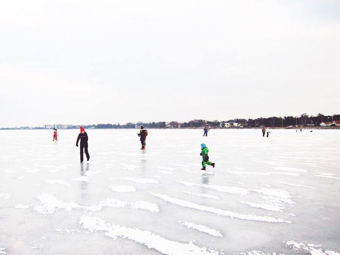 People on frozen lake against sky