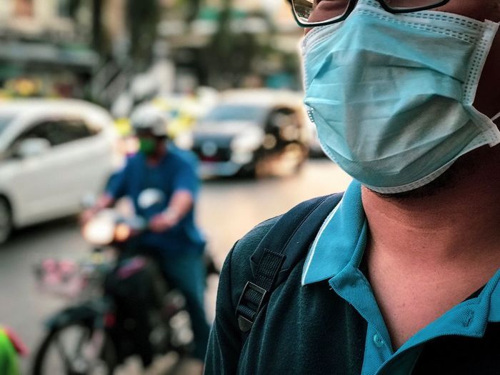 Close-up of man wearing surgical mask on street