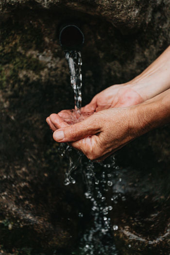 Hand holding water flowing from faucet