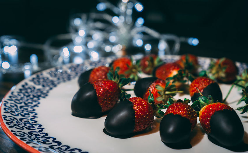 Strawberries on the plate covered with chocolate and decorated with lights.