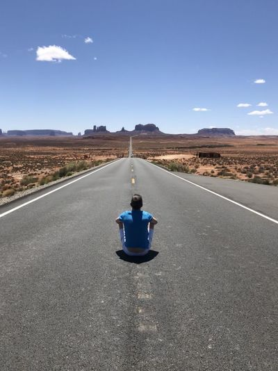 Rear view of man sitting on road against landscape