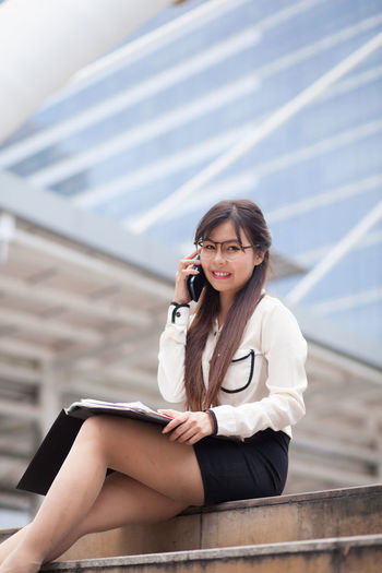 Portrait of businesswoman talking on mobile phone while sitting against office building