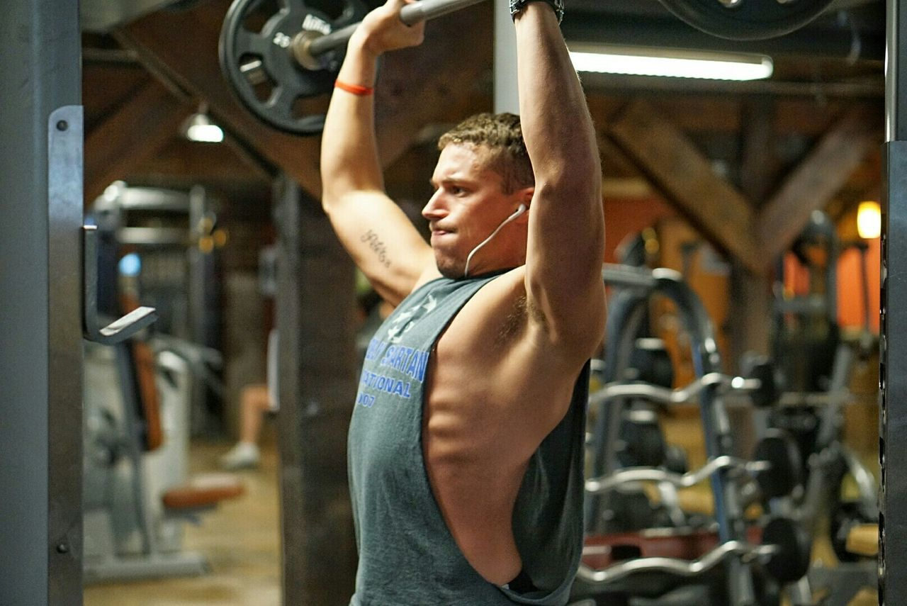 Young man lifting weights in gym