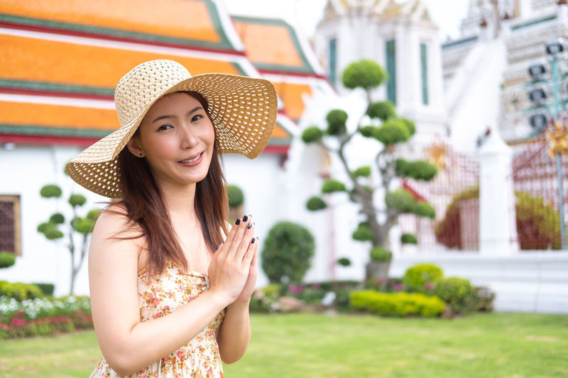Travel Thailand concept. Young Asian woman with smile greeting in thai style at Wat arun temple Asian  Greeting Thailand Travel Travel Photography Beautiful Woman Clothing Emotion Focus On Foreground Happiness Hat Looking At Camera One Person Outdoors Portrait Real People Smiling Sun Hat Teenager Thai Style Travel Thailand Travel Destinations Traveler Young Adult Young Women
