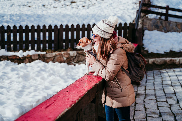 Woman holding dog on retaining wall during winter