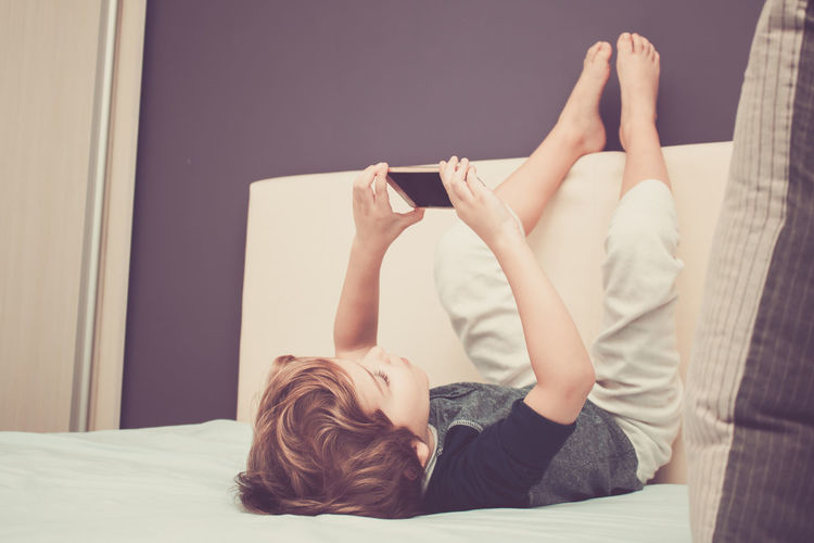 Boy with mobile phone lying on bed