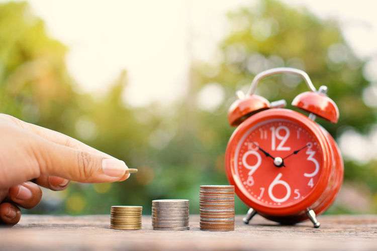Cropped image of hand stacking coins by orange alarm clock on table outdoors