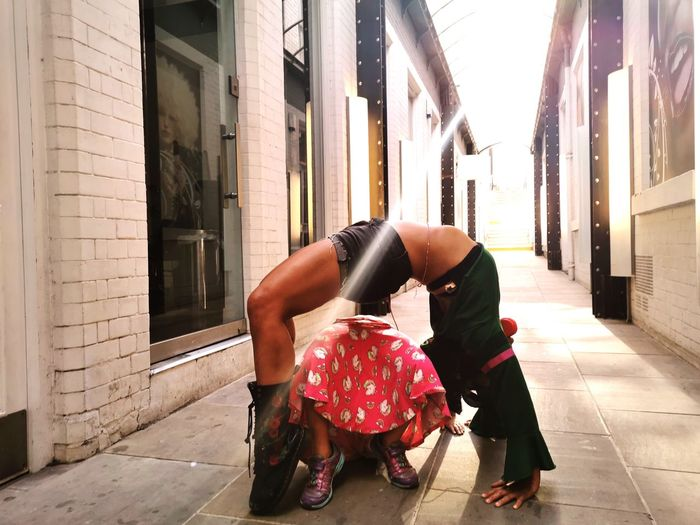 Side view of woman bending over backwards by daughter at alley in city