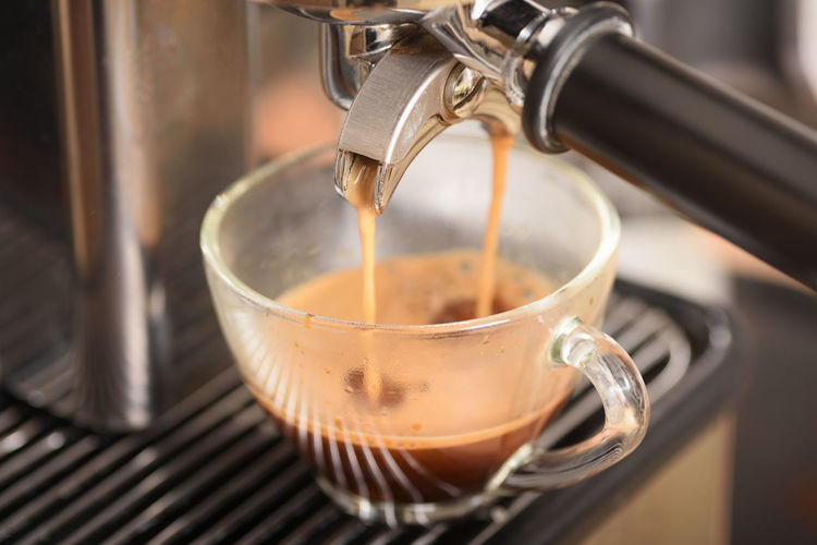 Close-up of coffee pouring in cup