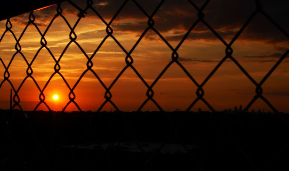 Backgrounds Beauty In Nature Chainlink Fence Dark Fence Focus On Foreground Idyllic Illuminated Landscape Nature No People Orange Color Outdoors Scenics Sky Sun Sunset Tranquil Scene Tranquility