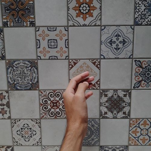 Cropped hand of man by tiled floor at home