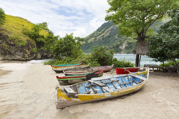 View of old brightly colored boats on Koka Beach in East Nusa Tenggara, Indonesia. ASIA INDONESIA Rural Swimming Tourist Travel Attraction Beach Boat Colorful Destination East Nusa Tenggara Explore Fishing Flores Island Koka Beach Landscape Ocean Paga Sea Southeast Asia Tourism Tropical Vacation