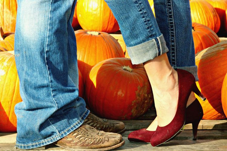 Low section of man and woman standing by pumpkins