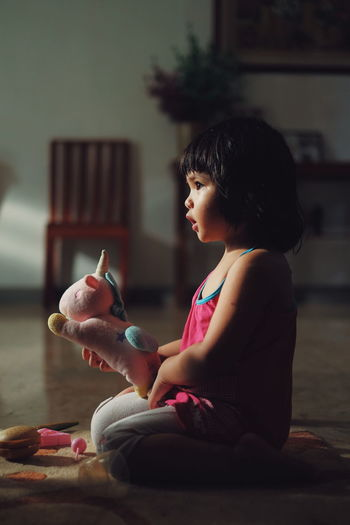 Side view of girl looking at toy at home