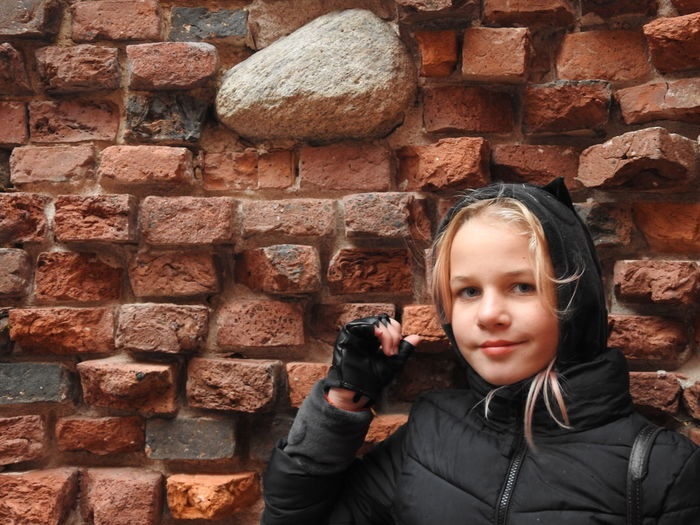 Portrait of girl against brick wall
