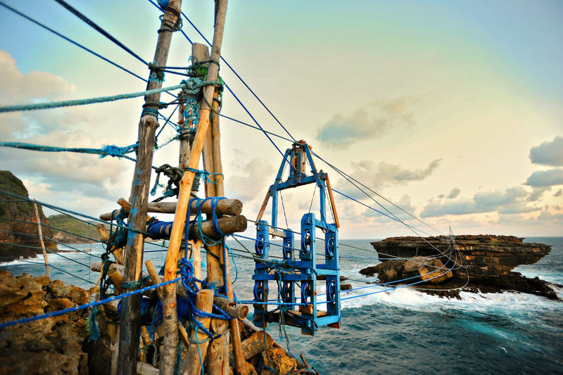 Hanging chair at Timang beach, Yogyakarta. Local fisherman usually use the hanging chair to cross the island to catch lobster. Beach Beauty In Nature Boat Deck Cloud - Sky Day Hanging Nature Nautical Vessel No People Outdoors Sailing Ship Scenics Sea Sky Travel Destinations Water