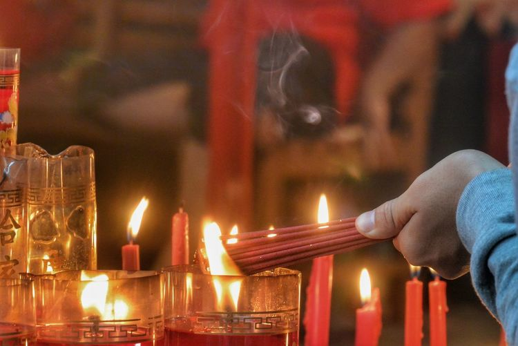 Cropped hand burning incense sticks on temple