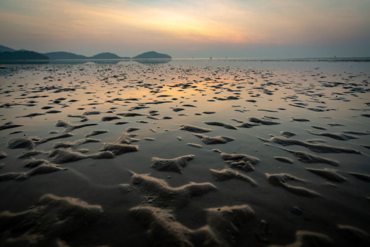 Sky Water Tranquility Beauty In Nature Sea Scenics - Nature Sunset Land Beach Tranquil Scene Nature Sand No People Idyllic Non-urban Scene Horizon Reflection Horizon Over Water Outdoors Surface Level