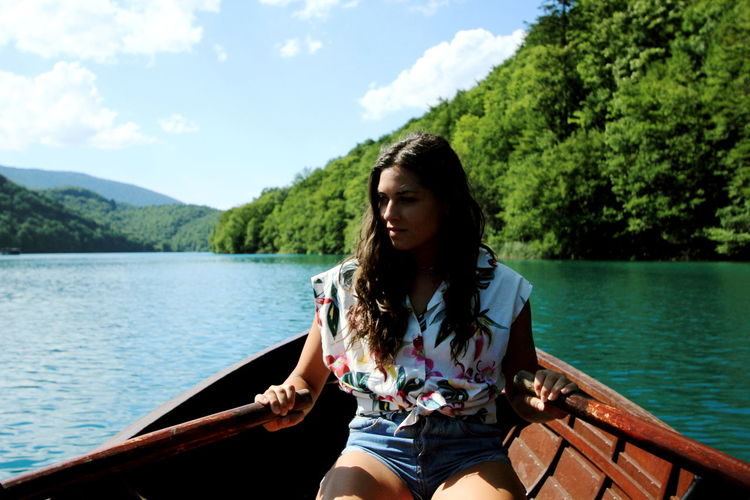 Young woman sitting on boat sailing in lake against sky